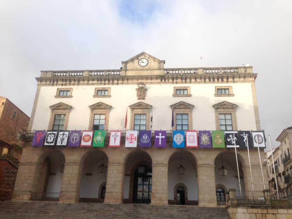 El balcón principal del Ayuntamiento luce los estandartes de las 17 cofradías de la Semana Santa cacereña